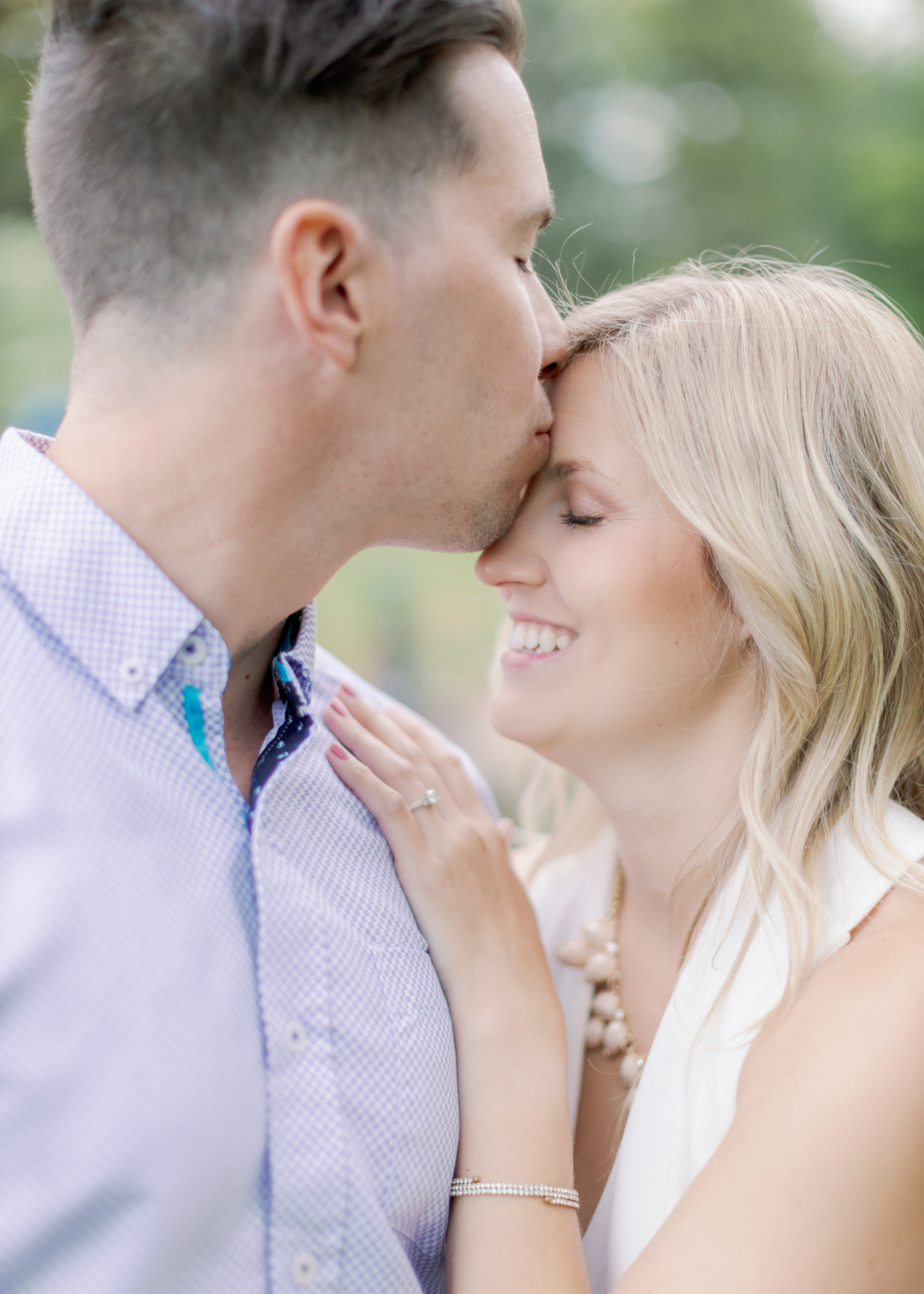 kiss on her forehead during engagement session